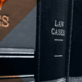 Books of law cases lined on a bookshelf.